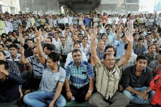 Textile traders chant slogans during a protest against GST in Surat on Thursday. Photo: PTI