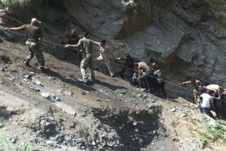 Police personnel and locals carry the injured and dead from the site of a bus accident in Ramban district on Sunday. Photo: AFP