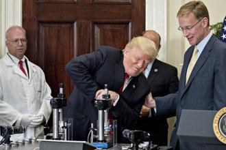 US President Donald Trump (centre) participates in a glass strength test of a Corning Valor vial with Wendell Weeks, chairman and CEO of Corning (right)in the White House, Washington DC, on Thursday. Photo: Bloomberg