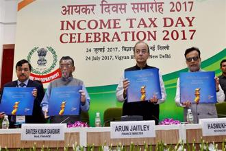 Union minister Arun Jaitley with MoS Santosh Gangwar, revenue secretary Hasmukh Adhia and CBDT chairman Sushil Chandra release a coffee-table book during Income Tax Day celebrations in New Delhi on Monday. Photo: PTI