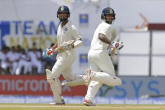 India's Cheteshwar Pujara, left, and Shikhar Dhawan run between wickets during the first day's play of the first test cricket match between India and Sri Lanka in Galle, Sri Lanka, on Wednesday. Photo: AP