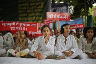 Children of farmers who have committed suicide hold placards during a protest in New Delhi on 19 July. Photo: AP