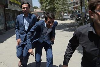 Locals run in panic at the site of a suicide blast near Iraq's embassy in Kabul on Monday. Photo: Shah Marai/AFP