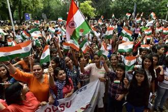 Students of Delhi University wave India flags during a 'Tiranga march' to mark 75 years of Quit India Movement at North Campus in New Delhi on Wednesday. PTI