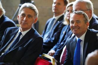 UK ministers Philip Hammond (L) and Liam Fox (right) have reconciled their differences by saying that a transition period following Brexit isn't a way for Britain to stay in the European Union 'through the back door'. Photo: Reuters