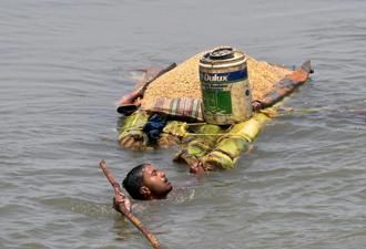 A villager carries grains on a raft as he shifts from a flooded village in Araria district of Bihar on Monday. Photo: PTI