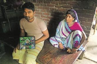 Bahadur Nishad with a photo of his son Deepak, one of the 30 children who died in BRD Hospital at Gorakhpur. Photo: Nikita Doval/Mint
