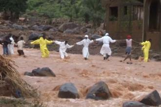 People wearing protective suits hold hands as they cross a river after a mudslide in the mountain town of Regent, Sierra Leone on 15 August. Photo: Reuters