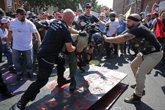 White nationalists, neo-Nazis, the KKK and members of the 'alt-right' attack each other during the melee outside Emancipation Park during the Unite the Right rally in Charlottesville, Virginia, on Saturday. Photo: AFP