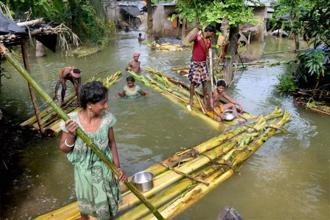 People commute on rafts at a flood-hit village near Balurghat in South Dinajpur district of West Bengal on Thursday. Photo: