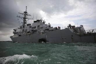 The dramatic pre-dawn accident sent water flooding into the USS John S. McCain, which limped into port in the city-state under escort later in the day. Photo: Reuters