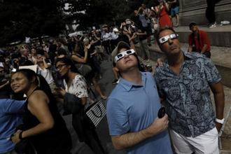 People looking at the sun during a solar eclipse near Columbus Circle in New York, US, on Monday. Photo: Bloomberg