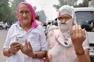 Two women show their fingers marked with ink after casting votes for Bawana assembly seat byelection in Delhi on Wednesday. Photo: PTI