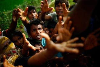 Rohingya refugees stretch their hands for food near Balukhali in Cox's Bazar, Bangladesh, on Monday. Photo: Mohammad Ponir Hossain/Reuters