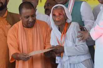 UP chief minister Yogi Adityanath gives a certificate to a farmer to clear his loans under the Uttar Pradesh government Farm Loan Waiver Scheme in Allahabad. Photo: PTI