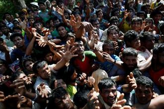 Rohingya refugees strech their hand for relief supplies given by local people in Cox's Bazar, Bangladesh. Photo: Reuters