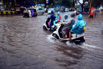Vehicles wade through a flooded road after heavy rains in Vashi, Navi Mumbai, on Tuesday. Photo: PTI