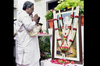 Karnataka chief minister Siddaramaiah pays floral tributes to Mahatma Gandhi on his 148th Birth Anniversay in front of Vidhan Soudha in Bengaluru on Monday. Photo: PTI