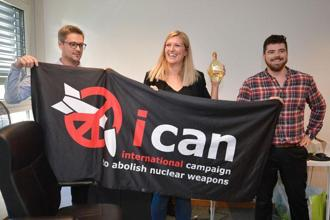 Nuclear disarmament group ICAN coordinator Daniel Hogstan, executive director Beatrice Fihn and her husband Will Fihn Ramsay pose with a banner bearing the group's logo after ICAN won the Nobel Peace Prize for its decade-long campaign to rid the world of the atomic bomb as nuclear-fuelled crises swirl over North Korea and Iran. Photo: Fabrice Coffrini/AFP