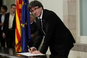 Catalan President Carles Puigdemont signs a declaration of independence at the Catalan regional parliament in Barcelona on Tuesday. Photo: Reuters