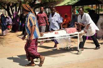 Somali men carry in a stretcher a man injured in the explosion of a truck bomb in the centre of Mogadishu, on 15 October, 2017. Photo: AFP