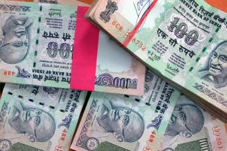 The rupee opened at 64.80 a dollar and touched a high and a low of 64.79 and 65.04 respectively. Photo: Bloomberg