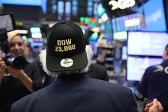 A trader wears a hat reading Dow 23,000 on the floor of the New York Stock Exchange on 17 October in New York City. Photo: AFP