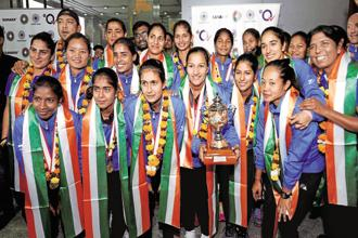 Members of the Indian women's hockey team which lifted the Asia Cup in Japan, at the Delhi airport on Tuesday. Photo: PTI