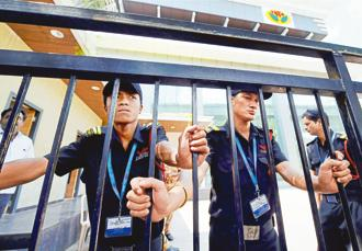 Private security persons stand guard near the main gate of Jaya TV where IT officials conducted a raid, in Chennai on Thursday.Photo: PTI