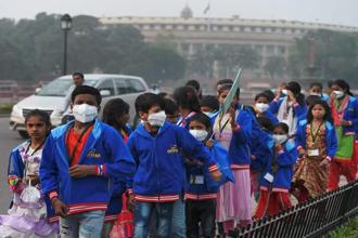 Children wearing air pollution masks attend a demonstration to spread awareness on the problem of air pollution on Children's Day in New Delhi on Tuesday. Photo: PTI