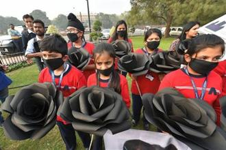 Children, wearing air pollution masks, hold replicas of black roses as they attend a demonstration to spread awareness about the problem of air pollution on Children's Day in New Delhi on Tuesday. Photo: PTI