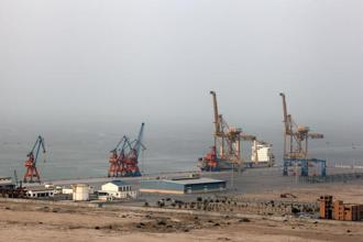 A cargo ship sits berthed next to a crane at Gwadar Port in Gwadar, Balochistan. Photo: Bloomberg