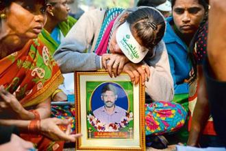 Vennela (centre) with her deceased father's photograph at a farmers' protest rally in New Delhi. Photo: Sayantan Bera/Mint