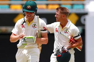 Australia's Cameron Bancroft (left) walks off the field with team mate David Warner after hitting the winning runs to win the first Ashes cricket test match against England in Brisbane. Photo: Reuters