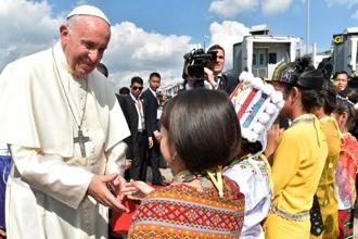 Pope Francis being greeted by children upon his arrival at Yangon International Airport on 27 November. Photo: AFP