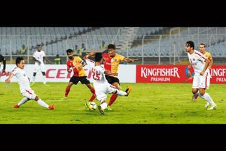 Defender Lalram Hmunmawia of Aizawl FC tackling East Bengal's forward Willis Deon Plaza during their opening match in Kolkata on 28 November.