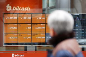 A pedestrian looks at a monitor showing the prices of virtual currencies at the Bithumb exchange office in Seoul on Friday. Photo: Bloomberg