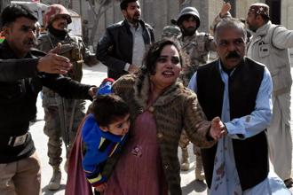 A policeman guides a family after gunmen attacked the Bethel Memorial Methodist Church in Quetta, Pakistan on Sunday. Photo: Reuters