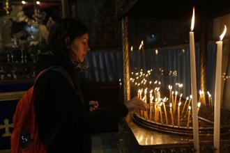 Christian worshipper lights candles at the Church of the Nativity, built atop the site where Christians believe Jesus Christ was born, on Christmas Eve, in the West Bank City of Bethlehem. Photo: AP