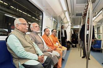 Prime Minister Narendra Modi takes a ride in a Metro from Botanical Garden Station to Okhla Bird Sanctuary along with Uttar Pradesh CM Yogi Adityanath and other dignitaries  on Monday. Photo: PTI