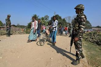 Villagers walk past CRPF personnel patrolling a road ahead of the publication of the first draft of the National Register of Citizens (NRC) in Juria village of Nagaon district of Assam. Photo: Reuters