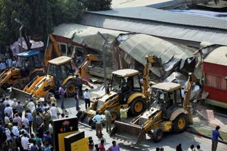 The BMC bulldozers take down illegally constructed eateries in the Kamala Mills compound following the fire incident in Mumbai on Saturday. Photo: PTI