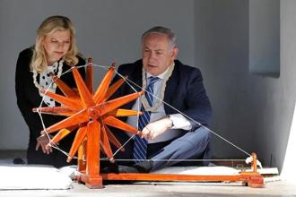 Israeli Prime Minister Benjamin Netanyahu spins cotton on a wheel as his wife Sara looks on during their visit to Gandhi Ashram in Ahmedabad on Wednesday. Photo: Reuters