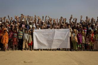 Rohingya children and refugees raise their hands and shout that they won't go back to Myanmar during a protest near Cox's Bazar in Bangladesh on 22 January, 2018. Photo: AP