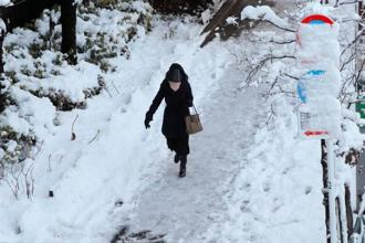 A woman makes her way on a snow-covered sidewalk in Tokyo, Japan, on Tuesday. Photo: Reuters