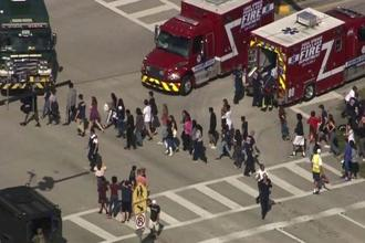 Students being rescued from Marjory Stoneman Douglas High School during a shooting incident in Parkland, Florida, on Wednesday. Photo: Reuters