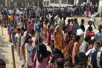 People stand in queues to cast their votes at a polling station on the outskirts of Agartala on Sunday. Photo: AP