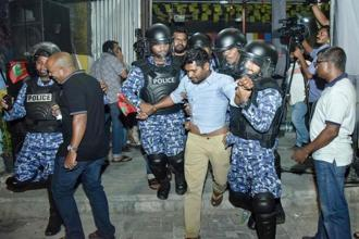 Maldivian police officers detain an opposition protestor demanding the release of political prisoners during a protest in Male. Photo: AFP