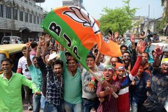 BJP supporters wave party flag to celebrate the party's win, which brought curtains down on 25 years of CPM rule, after Tripura assembly election results were announced in Agartala on Saturday. Photo: PTI