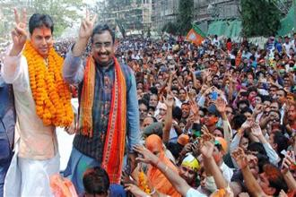 Tripura BJP chief Biplab Kumar Deb (left) and fellow party leader Ram Madhav celebrate with supporters after the party's victory in Tripura assembly elections on Saturday. Photo: PTI